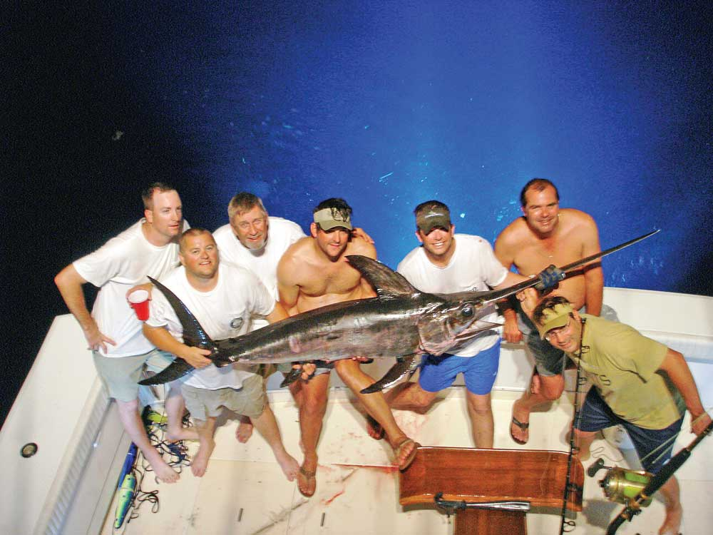 Anglers show their success in swordfishing at night.